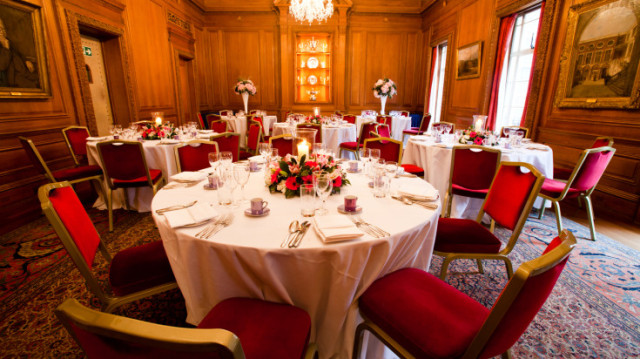 Livery Hall set with round tables dress in white linen and floral centre pieces for a dinner Brewers' Hall Christmas Party EC2