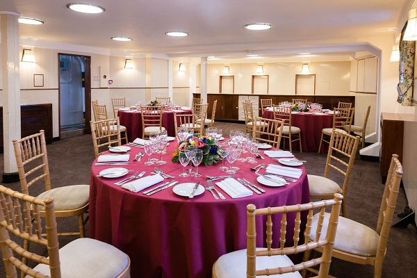 HMS Belfast Christmas Party Venue SE1. banqueting tables set up with furnishings