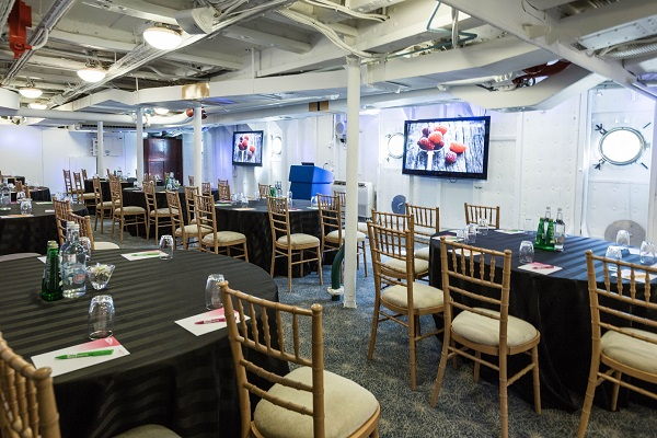 HMS Belfast Christmas Party Venue SE1. Inside of HMS Belfast, tables set out banqueting style