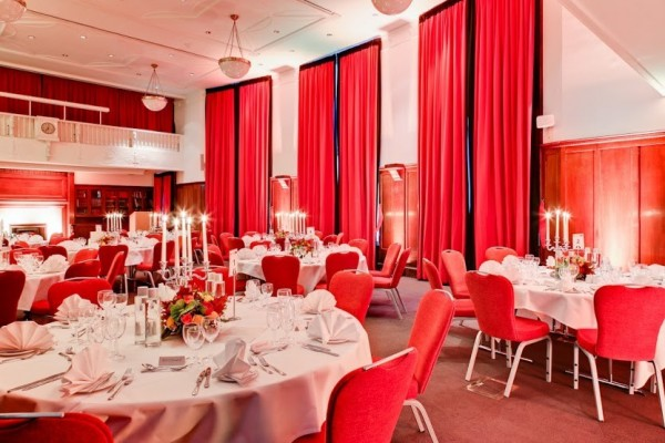 Council Chamber set for a large christmas party with high ceilings and round tables dressed with white table linen and place settings, grand curtains cover the venues large windows Hallam Christmas Party W1