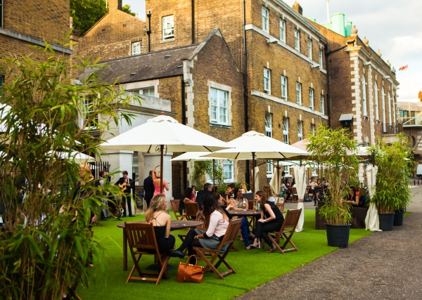 Tables and chairs under parasols HAC Armoury House Summer Party Venue EC1