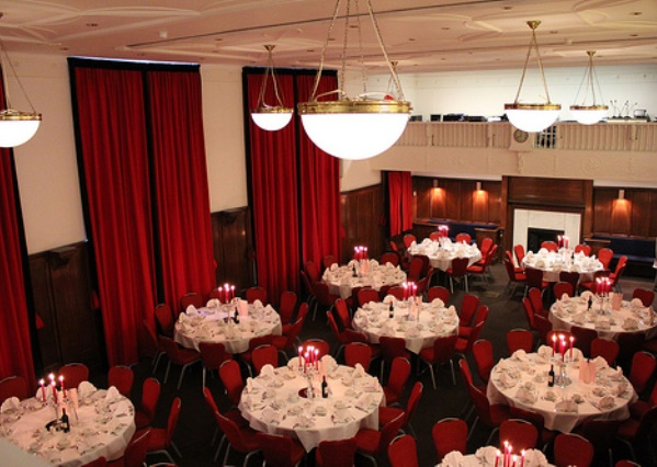 Council Chamber set for a large christmas party with high ceilings and round tables dressed with white table linen and place settings below Hallam Christmas Party W1