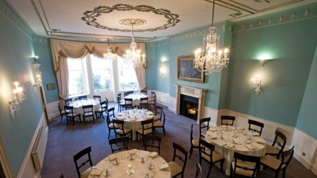 Sainsbury Room with grand high ceilings with intricate chandelier and open fireplace with round tables set for dinner and dressed in white linen 28 Portland Place Christmas Party W1
