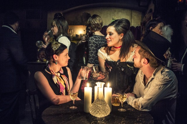 Actors dressed up in scary attire at a candle lit table London Dungeons Shared Christmas Party Venue SE1