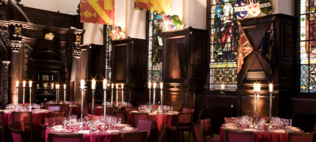 Stationers' Hall Christmas Party EC4, old hall with lights and dining tables with candles on