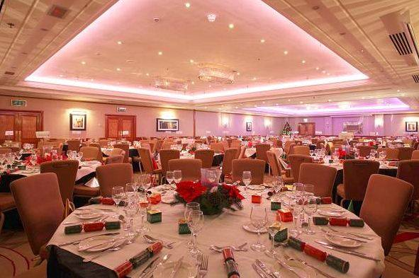 Round tables dressed with white linen and Christmas crackers set up for a Christmas party in the Hyde Park Suite Amba Marble Arch Christmas Party W1