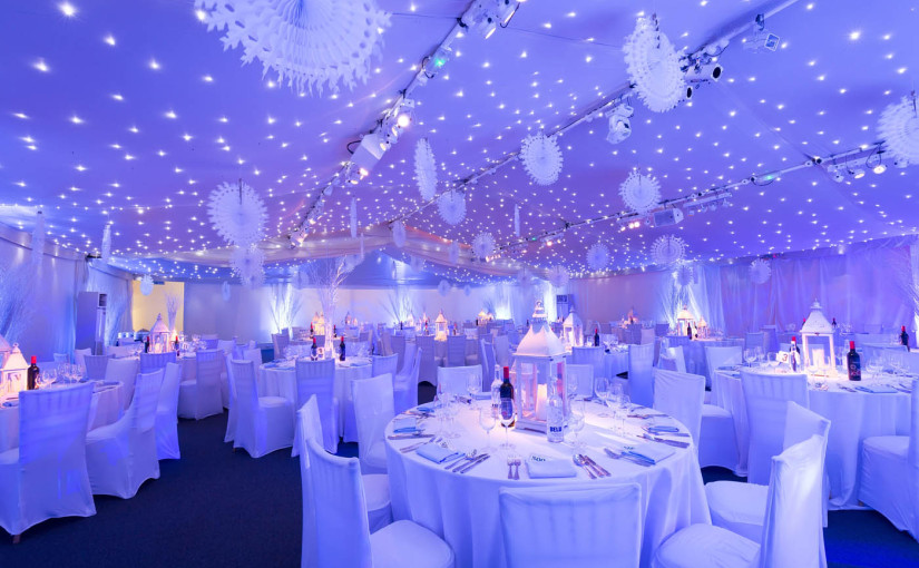 Conservatory at Painshill Christmas Party KT11, ceiling lighting, lilac colour wash throughout the room, large circle tables for a seated dinner