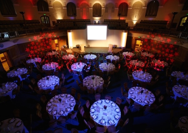 Church House Christmas Party Venue SW1, Large space with round tables laid for dinner a big screen against one wall