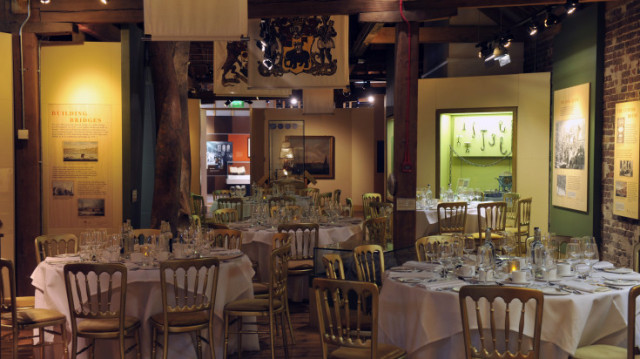 Galleries set for a dinner party with round tables dressed in white linen Museum of Docklands Christmas Party E14