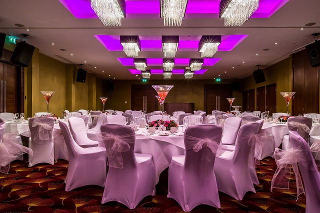 Kensington Close Hotel Shared Christmas Party, seated dinner set up, rounds of 10 and dance floor, colour wash, festive novelties