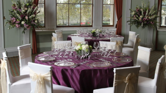Library set for a Christmas meal with round tables dressed in purple linen and smart chair covers with foral centre pieces and natural daylight Trinity House Christmas Party EC3
