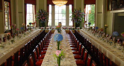 Library set for a large banquet with floral centre pieces are large windows with natural daylight Trinity House Christmas Party EC3