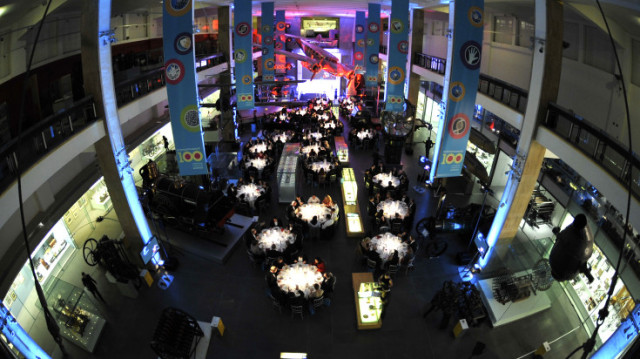 Making the Modern World birds eye view with large round tables set for dinner with bright lights shone on to the tables Science Museum Venue Hire SW7