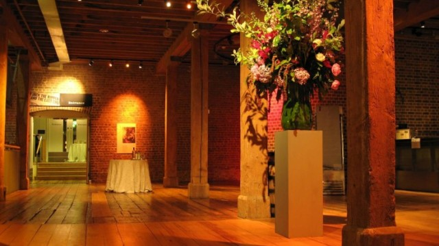 Muscovado Hall with view to the rum store event space with wooden pillars and large floral centre pieces Museum of London Docklands Venue Hire E14