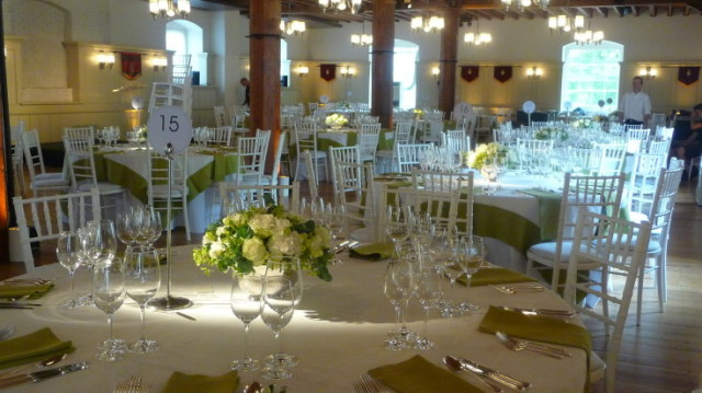 New Armouries Banqueting Suite set for a dinner with elegant glassware and floral centre pieces with round tables between oak pillars Tower of London Venue Hire EC3