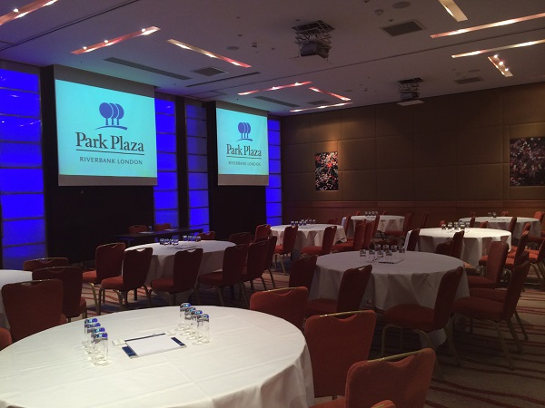 Park Plaza Riverbank Christmas Party SE1. Tables set up banqueting style with festive lighting and screens with hotels name on screens