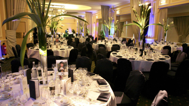 Prince Albert Suite set for a dinner with round tables, large floral centre pieces and white linen with chair covers ZSL London Zoo Venue Hire NW1