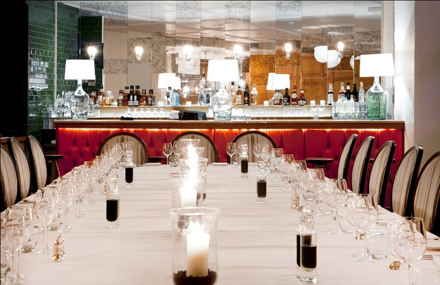 Hush Mayfair Venue Hire W1. Long dining room table set out with a contempary feel with bar infront.