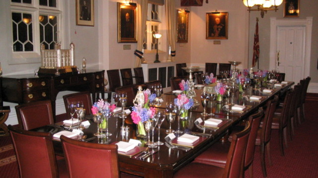 Royal Regiment of Fusiliers set for a private Christmas dinner with large oak boardroom tables and historic portrait hanging paintings Tower of London Christmas Party EC3
