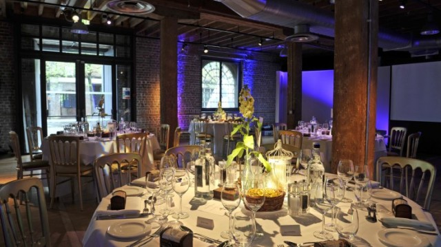 Rum Store set for a private dinner with round tables dressed in white linen and floral centre pieces Museum of Docklands Christmas Party E14