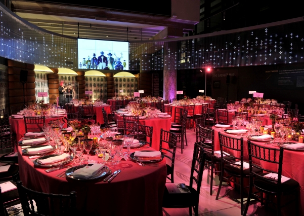 Sackler Hall with round tables set for a large gala dinner with mood lighting and large presentation facilities Museum of London Christmas Party EC2