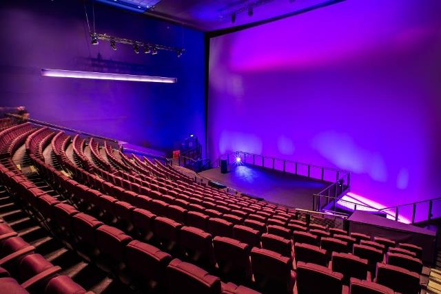 IMAX Cinema with tiered seating and large cinema screen illuminated with purple lighting perfect for conferences Science Museum Venue Hire SW7