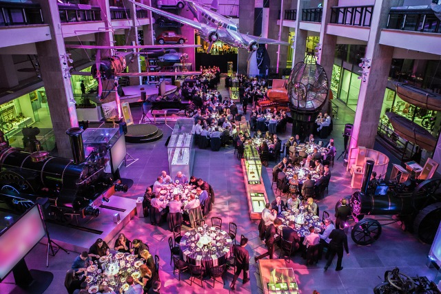 Making the Modern World birds eye view with large round tables set for dinner with coloured uplighters Science Museum Venue Hire SW7