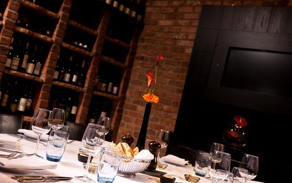 Malmaison Edinburgh Christmas Party EH6, private dining table with brick walls and a orange table flower