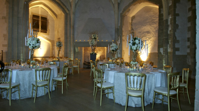 Upper Wakefield Tower Suite set for a dinner party with large exposed brick archways and round tables dressed in white linen with eccentric centre pieces Tower of London Christmas Party EC3