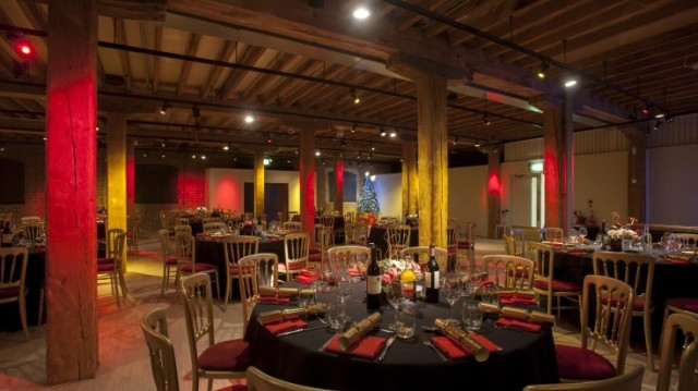 Chris Ellmers Galleries set for a christmas dinner with red colour theme on black round table linen wit views of the high wooden beams Museum of Docklands Christmas Party E14