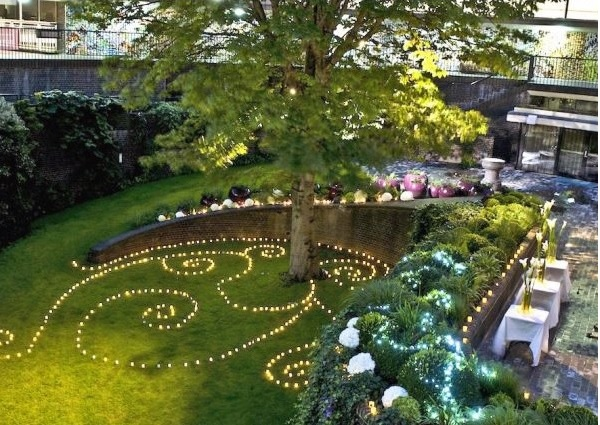 Terrace Garden Room lit with swirling fairy lights on the grass below the trees Museum of London Summer Party EC2Y