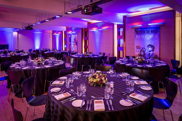 Churchill War Rooms Christmas Party SW1. Large space with decorative lighting asnd large round tables set up for dining.