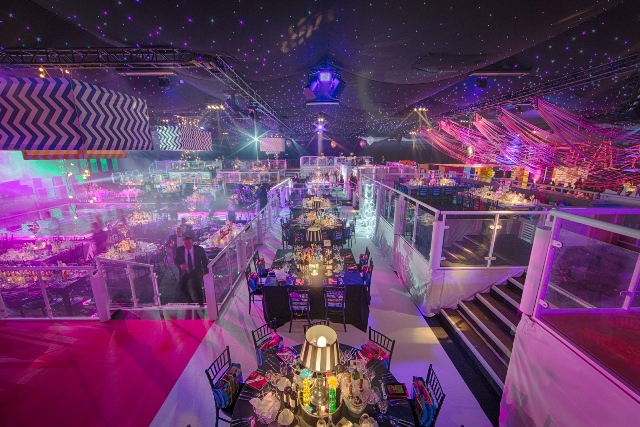 Battersea Evolution Venue Hire SW11 set up for an awards dinner with stage lighting and round tables with centre pieces