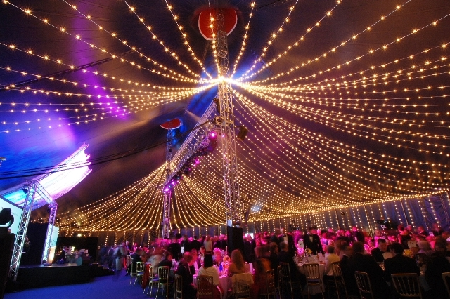 View of the marquee decorated with fairy lights with round tables dressed for dinner below Bloomsbury Big Top Christmas Party WC1