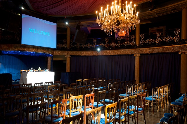 Cafe de Paris Venue Hire W1. Conference room, Theartre style. With screen and hanging chanderlier.