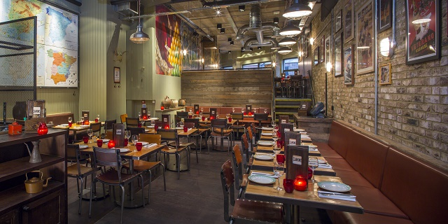 Camino Blackfriars Venue Hire EC4. Restaurant with spanish decor and single tables and chairs for dining with DJ booth high up Camino Blackfriars Venue Hire London, EC4