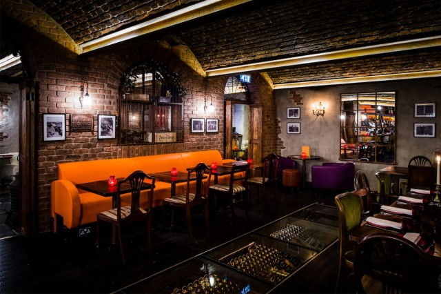 View of the underground private room Copa de Cava with exposed brick work and informal and brightly coloured sofa seating with private bar Camino Blackfriars Venue Hire London, EC4