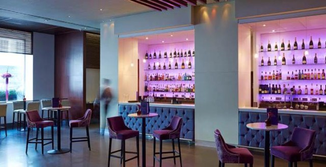 View of the venue's bar with formal leather high seating and tables with view of the bar Cumberland Hotel Venue Hire W1