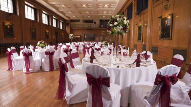 Edward Lumley Hall set for a Christmas party dinner with natural lighting and round tables with white linen and chair covers with bows boasting grand high ceildings Royal College of Surgeons Christmas Party WC2