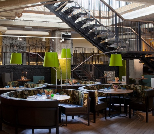 Folly Christmas Party EC3. showing staircase of The Folly with green lights and round tables are banqueting style.