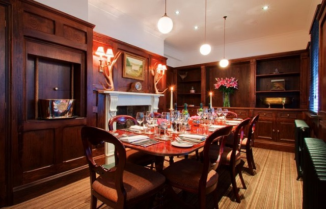 View of the private dining room set for dinner surrounding wooden walls and fire place Hat and Tun Venue Hire EC1