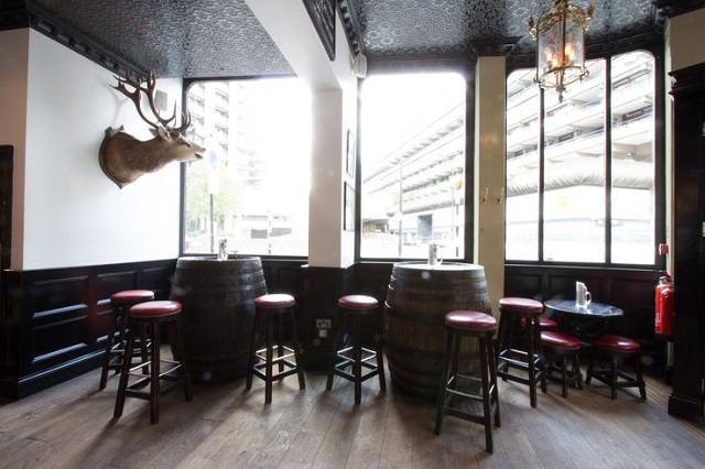 View of the Bar area with informal barrel seating and deer head wall hanging Jugged Hare Venue Hire EC1