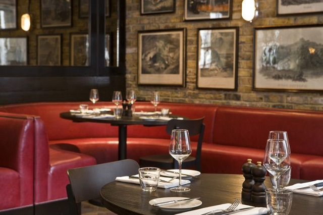 Dining Room with exposed brick work and red sofa informal seating with tables set for dinner Jugged Hare Venue Hire EC1