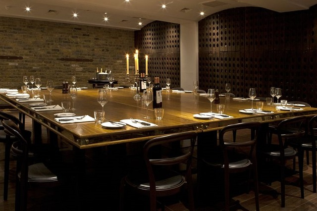 View of the Josephine Room set for a private dinner with fixed large oak tale and exposed brick work Jugged Hare Venue Hire EC1