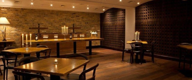 Restaurant set for Christmas drinks reception with candles and exposed brick work Jugged Hare Christmas Party EC1