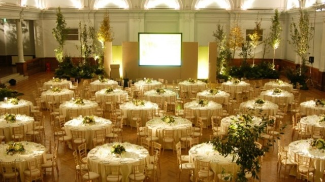Gala Dinner set up with large round tables dressed in white linen with large presentation screen facing the front of the room with the venue decorated with floral bouquets and centre pieces and up lighters around the room Lindley Hall Venue Hire SW1