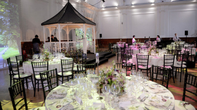 Lindley Hall set up for a wedding with a purpose built alter at the front of the room and round dressed in white table linen and floral centre pieces surrounding it Venue Hire SW1