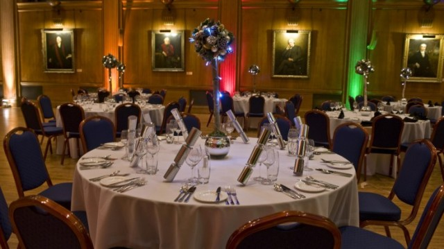 Edward Lumley Hall set for a Christmas party dinner with mood lighting and round tables with white linen and chair covers with bows boasting grand high ceildings Royal College of Surgeons Christmas Party WC2