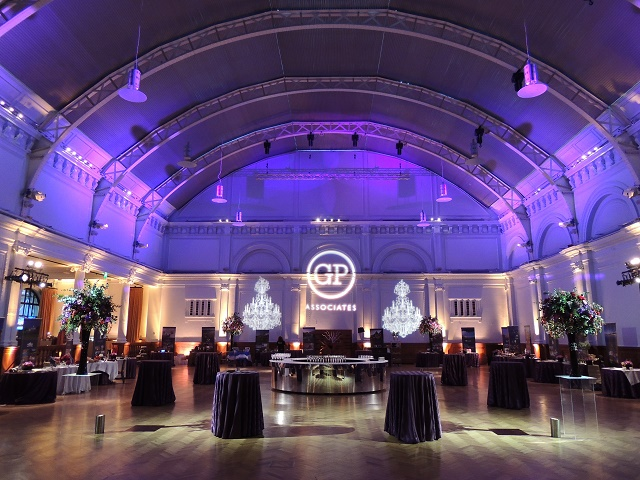 Drinks Reception set up with large poseur tables draped in dark linen dotted around the venue with purple uplighters illuminating the hall Lindley Hall Venue Hire SW1