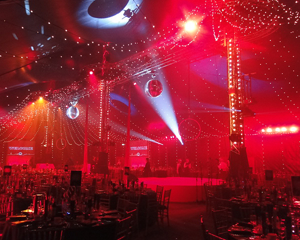 View of the marquee with stage lighting and round tables dressed for dinner Bloomsbury Big Top Christmas Party WC1